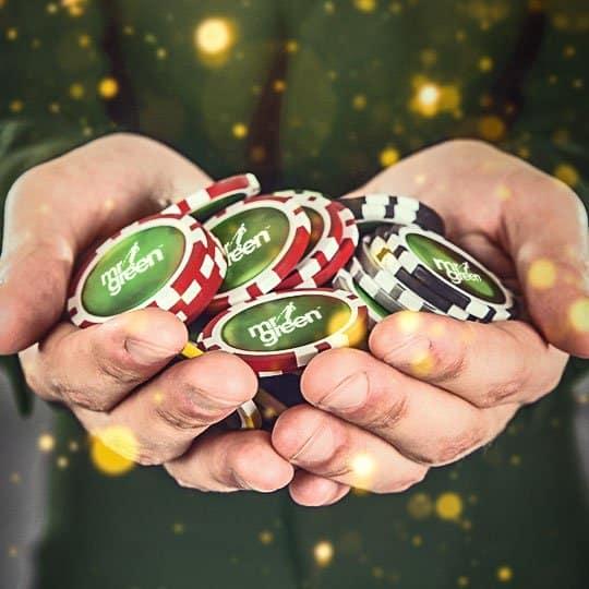 Karaktären Mr Green håller i flera spelmarker med casinots logo