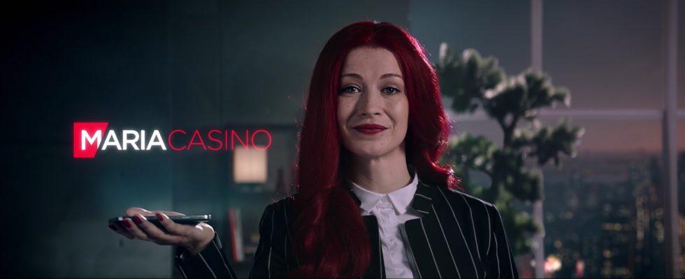 kvinna med rött långt hår som håller upp sin hand med logon för Maria Casino över