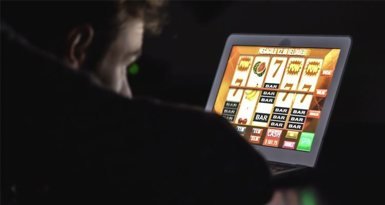 En man som stirrar på dataskärmen med ett slotspel snurrandes