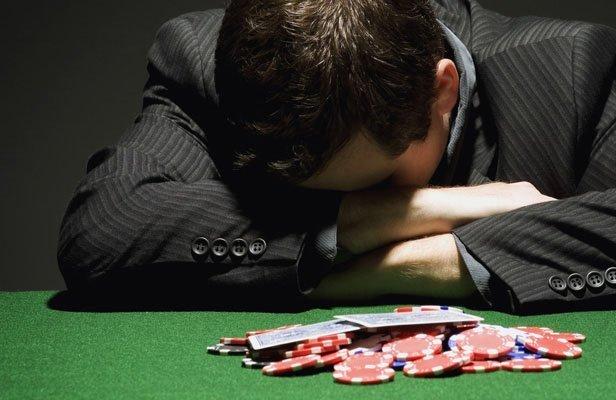 Spelberoende person som är ledsen efter en förlust på poker