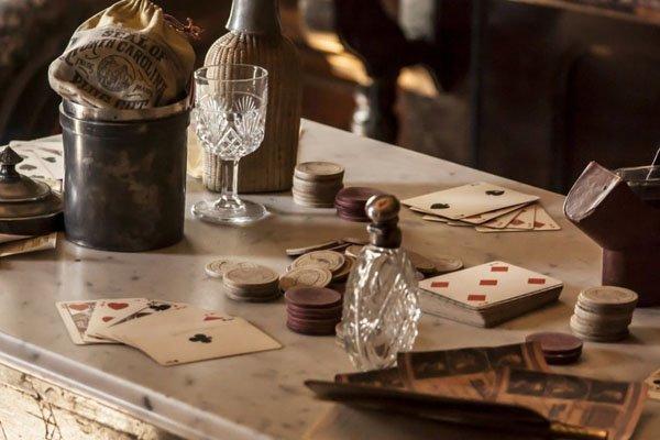 Ett gammeldags bord med pengar, spelkort och vinglas