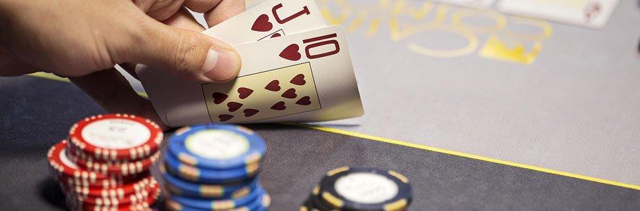 En hand som håller upp två kort under ett poker-spel med pokermarker på sidan om