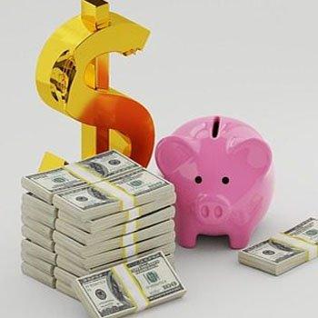 Pengasedlar i bunt brevid ett dollartecken och en spargris