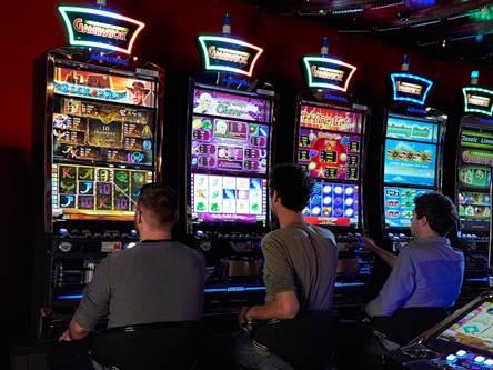 Tre män som sitter framför spelmaskiner i ett landbaserat casino