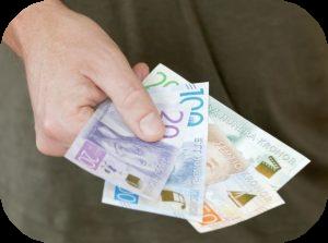 hand som håller olika svenska sedlar