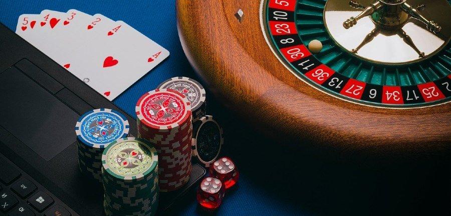 Roulettehjul brevid en dator och spelmarker och kort
