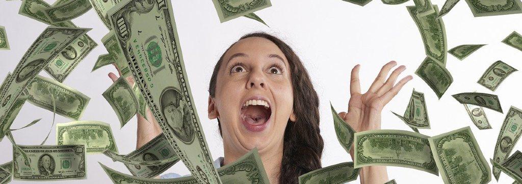 Glad kvinna med pengar som regnar över henne